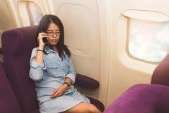Utilisation asiatique de femme de téléphone portable à l'intérieur d'avion Image stock