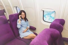 Utilisation asiatique de femme de téléphone portable à l'intérieur d'avion Photos stock