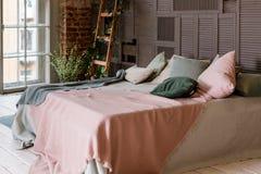 Utilisation créative du petit espace dans un intérieur élégant de chambre à coucher avec le décor de concepteur et la literie bla photo stock