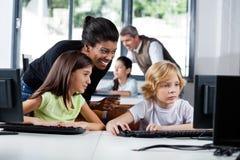 Utilisation d'Assisting Schoolchildren In de professeur féminin photos libres de droits