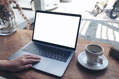 Utilisation d'une main et ordinateur portable émouvant avec l'écran de bureau blanc vide sur la table en bois en café Images stock