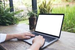 Utilisation d'une main et ordinateur portable émouvant avec l'écran de bureau blanc vide sur la table en bois en café Photos stock