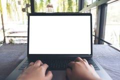 Utilisation d'une main et ordinateur portable émouvant avec l'écran de bureau blanc vide sur la table en café Image libre de droits