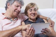 Utilisation de comprimé de Digital des couples des personnes supérieures Image libre de droits