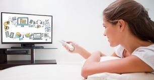 Utilisation de femme à télécommande avec de diverses icônes sur l'écran de TV Photo libre de droits
