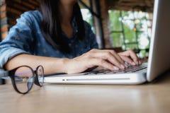 Utilisation de femme d'affaires en ligne par l'intermédiaire de l'ordinateur portable Images stock