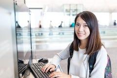Utilisation de femme d'ordinateur dans l'aéroport Image stock