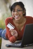 Utilisation de femme de couleur par la carte de crédit et ordinateur portatif à l'extérieur Photo stock