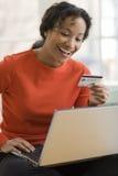 Utilisation de femme de couleur par la carte de crédit et ordinateur portatif photographie stock libre de droits