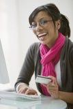 Utilisation de femme de couleur par la carte de crédit pour le commerce électronique Photo libre de droits