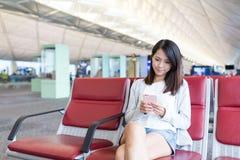 Utilisation de femme de téléphone portable dans l'aéroport Photographie stock libre de droits