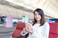 Utilisation de femme de téléphone portable dans l'aéroport Photos stock