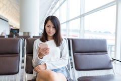 Utilisation de femme de téléphone portable dans l'aéroport Image libre de droits