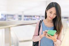 Utilisation de femme de téléphone portable dans l'aéroport Image stock