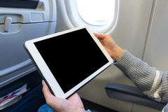 Utilisation de femme du comprimé numérique dans l'avion Photos stock