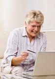 Utilisation de femme par la carte de crédit pour acheter des marchandises d'Internet Photographie stock libre de droits