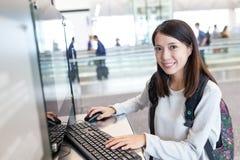 Utilisation de jeune femme d'ordinateur public dans l'aéroport Photo stock