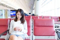 Utilisation de jeune femme de téléphone portable dans le secteur de départ de l'aéroport Image stock