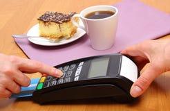 Utilisez le terminal de paiement pour payer le gâteau au fromage et le café en café, concept de finances photographie stock libre de droits