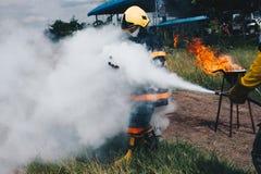 Utilisez un extincteur pour mettre le feu aux sapeurs-pompiers photos libres de droits