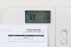 Utility bill with heating thermostat on wall. Close up of home heating thermostat with partial utility bill on wall Stock Photo