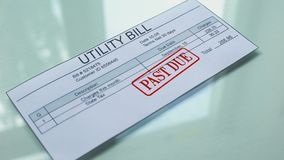 Utility bill past due, hand stamping seal on document, payment for services