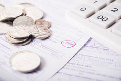 Utility bill with silver coins and calculator Royalty Free Stock Photography