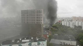 Utility building is on fire. Open fire and plume of smoke rises above ground and buildings around.