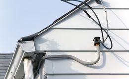 Utility Cables. Household utility cables on the side of a family home Royalty Free Stock Image