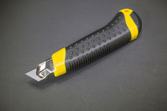 Utility knife with yellow plastic handle and black rubber insert Stock Photography