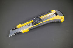 Utility knife with yellow plastic handle and black rubber insert Stock Image