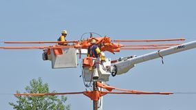 Utility linemen work on a high voltage line royalty free stock images