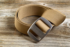Utility nylon belt with buckle on rustic wooden boards. Close up view of a brand new utility belt with large buckle on rustic wooden boards Royalty Free Stock Image