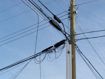 Utility pole confusing power cable phone line mess. Wooden pole hung with confusing and messed-up electricity power cables and telephone lines for residential royalty free stock photos