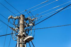 Utility pole or power pole. Column with electric disconnect power. Blue clear sky. Three-phase power line connection. Royalty Free Stock Images