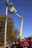 Utility Pole Work. An electrical worker adds a new line to a utility pole Stock Photo