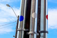 Utility poles with dots and light fixture. City utility poles with blue white and red dots with city light fixture in the background with blue sky and white royalty free stock photo