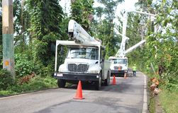 Utility trucks help workers restore electrical power near Palmer, Puerto Rico after Hurricane Maria. Utility trucks with aerial lifts help electrical workers Stock Photos