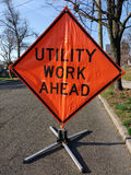 Utility Work Ahead. Orange and black sign telling motorists to be aware that there is utility work ahead. This sign is positioned in the street, near the curb Stock Photos