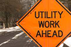 Utility work ahead. Road construction warning sign on a winter road in a residential neighborhood stock photography