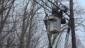 Utility worker works from a bucket near powerlines