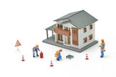 Utilização modelo da casa diminuta do modelo do reparo A do trabalhador da construção dos povos como o conceito dos bens imobiliá imagem de stock