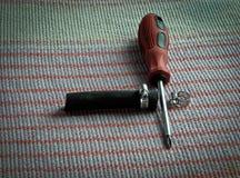 Utiliza ferramentas a chave de fenda, aperta as braçadeiras e a mangueira de borracha na tabela fotografia de stock