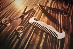 Utiliza ferramentas o barbeiro em um fundo de madeira Fotos de Stock Royalty Free