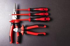 Utiliza ferramentas o eletricista em um fundo preto Utilize ferramentas para a chave de fenda de trabalho, alicates, platypuses Foto de Stock