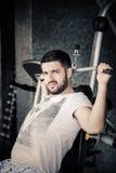 A utilização do homem puxa para baixo a máquina no ginásio O homem muscular considerável que exercita sobre puxa para baixo a máq Imagens de Stock