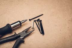 Utilize ferramentas a chave de fenda, o parafuso e os alicates em um fundo de madeira Fotos de Stock Royalty Free