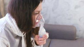 Utilizzi il nebulizzatore e l'inalatore per il trattamento Giovane donna che inala attraverso la maschera dell'inalatore Fronte d video d archivio