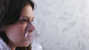 Utilizzi il nebulizzatore e l'inalatore per il trattamento Giovane donna che inala attraverso la maschera dell'inalatore Fronte d stock footage