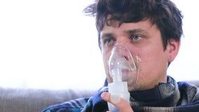 Utilizzi il nebulizzatore e l'inalatore per il trattamento Uomo malato che inala attraverso la maschera dell'inalatore video d archivio